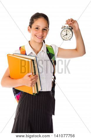 Happy schoolgirl standing with book and alarm clock in hands, isolated on white