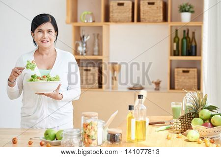 Smiling Vietnamese woman with a bawl of fresh salad