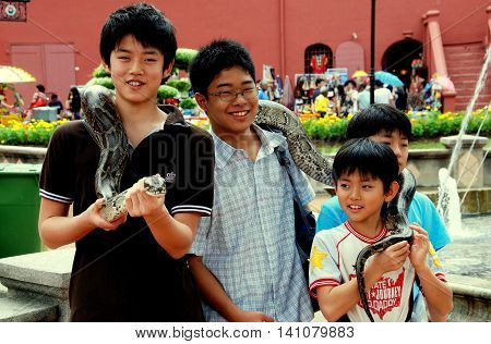 Melaka Malaysia - December 27 2007: Four Asian boys pose with a giant snake wrapped around their shoulders in Stadthuys Square