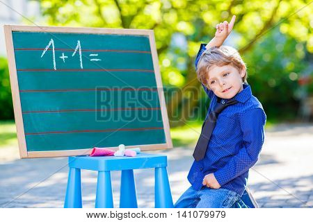 Adorable funny little kid boy at blackboard practicing counting and math, outdoor school or nursery. Child having fun with learning. Back to school concept.