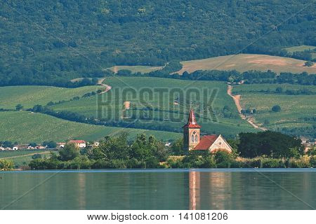 The island with the old church in the middle of the lake. Landscape under Palava. Czech Republic - South Moravian Region wine region. Water tank - New Mills - Pasohlavky.