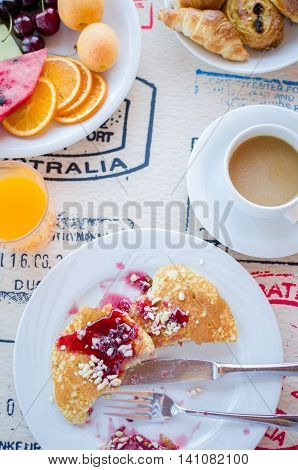 Breakfast including pancakes with raspberry jam, coffee, orange juice, pastries and fruits. Healthy breakfast. Good morning. Breakfast table. Morning breakfast with classic pancakes and jam. Top view.