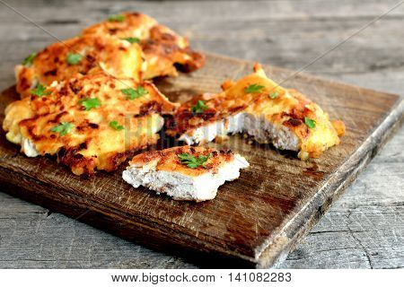 Turkey meat pieces fried in batter and garnished with parsley leaves. Cut roasted Turkey cutlets on a cutting board and an old wooden background. Cooking poultry product