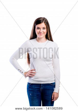 Teenage girl in white sweater, arm on hip. Young beautiful woman, studio shot on white background, isolated.