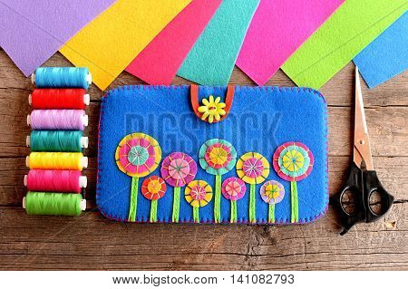 Handmade case for tablet. Felt blue case with bright flowers, thread kit, felt sheets, scissors on old wooden background. Sewing DIY for tablet computer. Top view. Closeup