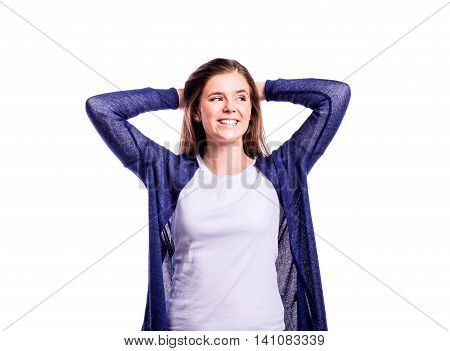 Teenage girl in white t-shirt and blue cardigan, touching hair, smiling. Young beautiful woman, studio shot on white background, isolated