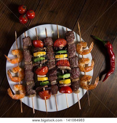Skewered meat, shrimp and vegetables on a plate, Studio shoot