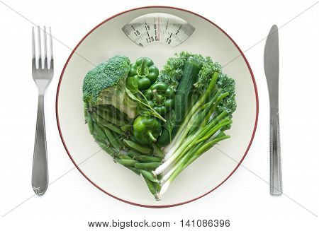 Weighing scales plate with green vegetables over a white background