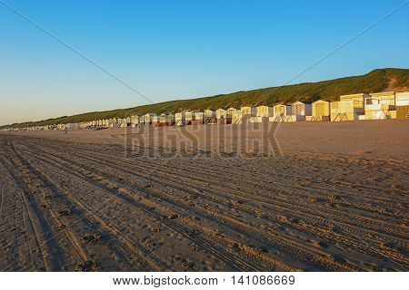 On the beach near the dunes a row of beach huts in the rays of the sunset.