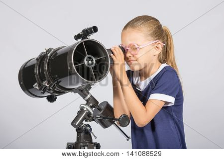 Seven-year Girl In Glasses With Interest Looks In A Reflector Telescope