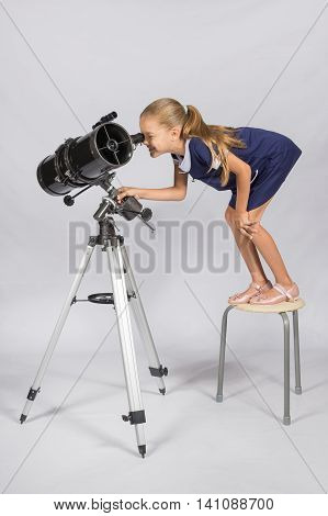 The Young Astronomer Standing On A Chair And Funny Looking In A Telescope Eyepiece