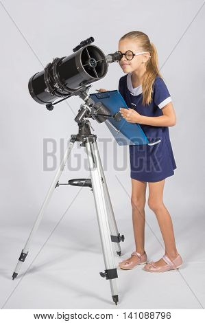 The Young Astronomer In Glasses With Interest Peers Into The Eyepiece Of The Telescope