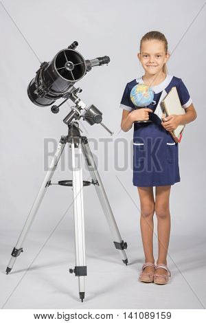 Schoolgirl Astronomer Is A Telescope With A Globe And Books In The Hands