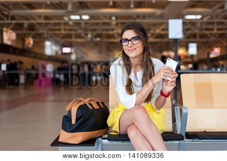Casual young woman using her cell phone while waiting to board a plane at the departure gates.