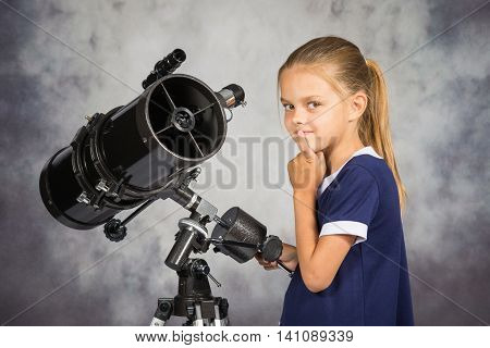 Seven-year Girl Thoughtfully Looks In The Picture, Standing At The Telescope