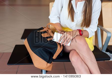 Body parts close-up. Young woman holding her cell phone while sitting, waiting to board a plane at departure gates.