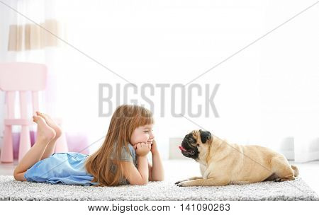 Cute girl playing with dog on carpet