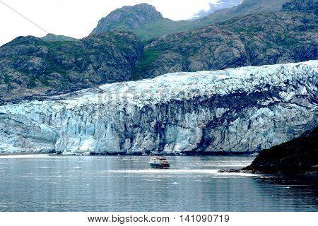 A small boat takes a closer look at the Margene Glacier in Glacier Bay Alaska