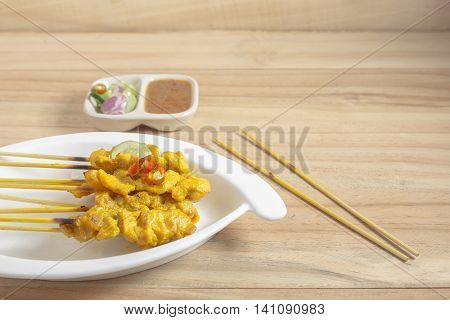 A grill pork satay with peanut sauce in white dish on wooden floor.
