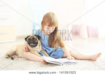 Cute girl reading book with dog on carpet