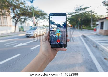 California, United States - July 16, 2016: Hand holding a cellphone to play Pokemon Go with blur road background