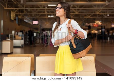 Young woman with a hand bag in casual wear holding his luggage while sitting in the hall of the airport waiting for his flight.