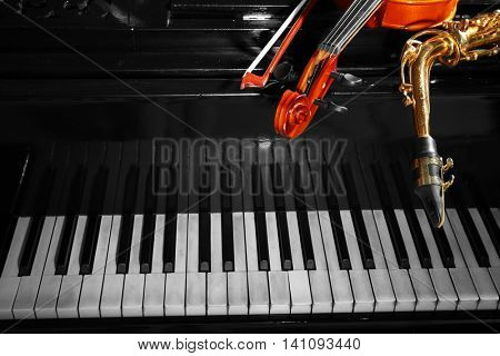 Violin with saxophone and piano, closeup