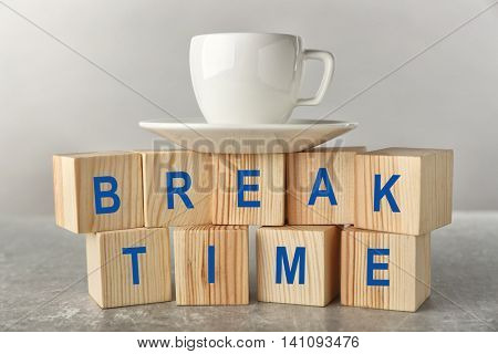 Words BREAK TIME and cup of tea on grey background