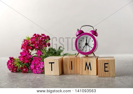 Word TIME with clock and flowers on grey background