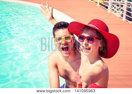 Beautiful couple having fun taking selfie at swimming pool - Cheerful friends enjoy mobile photo camera using stick on sunny day - Concept of happy moments on board of touristic ship
