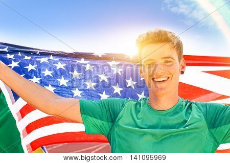 Young american man holding usa national flag outdoors - Cheerful sport fan with sun back lighting is celebrating victory at athletic stadium track - Concept of joyful moment at competitions and events