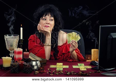 Middle-aged woman predicting future with fortune telling cards. Fortuneteller shows three cards to monitor during internet session. Black-haired woman wears red blouse. There are some cards and candles at the desk