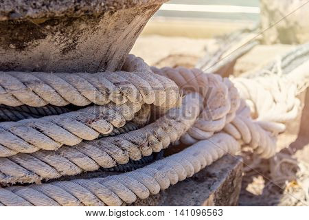 Old thick naval Rope on a Pier with sun flare