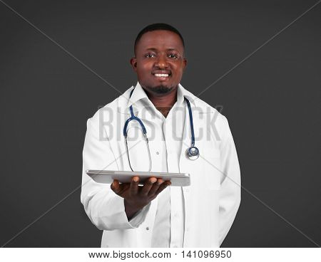 Professional African doctor on dark background