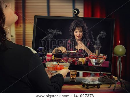 Woman in trance has internet video session with experienced middle-aged female fortuneteller. The psychic holds yellow burning candle over the water and looks at her client from monitor