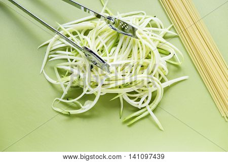 Courgetti spiralized zucchini on green chopping board with spaghetti and stainless steel serving tongs