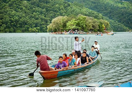 Pokhara Nepal - July 25, 2011: Tourists enjoy boat ride in vast Phewa Lake, natural colors. Phewa lake is a tourist spot located at an altitude of 742 m