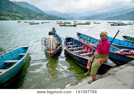 Pokhara Nepal - July 25, 2011: Tourists enjoy boat ride in vast Fewa Lake, natural colors. Pokhara is a popular tourist destination known for trekking and boating.