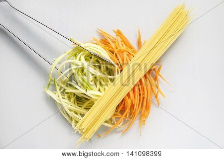 Spiralized zucchini courgette and carrot as a healthy substitute for the spaghetti lying on top with stainless steel serving tongs