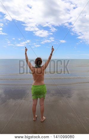 Young woman with thumb up on the seashore in the summer