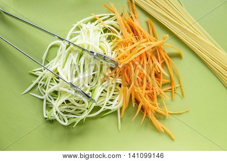 Courgette zucchini and carrot spirals showing a healthy alternative to spaghetti on green chopping board