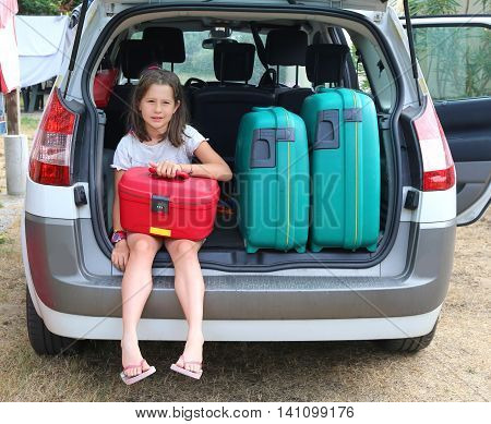 Beautiful Little Girl With Brown Hair Loads The Red Suitcase