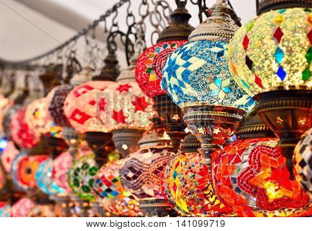 Turkish or oriental lamps on a bazaar with selective focus on the foreground. Multicolored lamps or lanterns with copy space.
