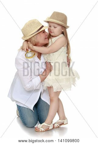Cute little girl with long blond hair in white dress and hat . The girl girl hugging his neck his grandmother - Isolated on white background