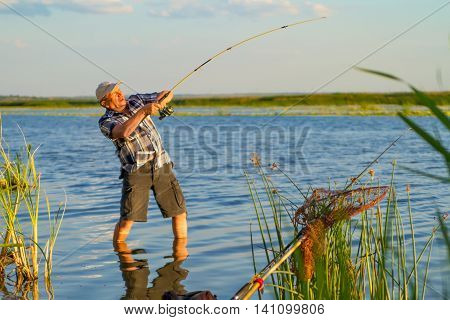 a fisherman with a fishing rod is catching a big fish on a nice sunny day