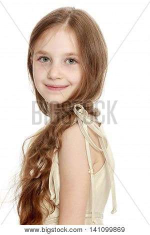 Beautiful little girl with long brown hair to her waist . The girl smiles sweetly turning sideways to the camera. Close-up - Isolated on white background - Isolated on white background