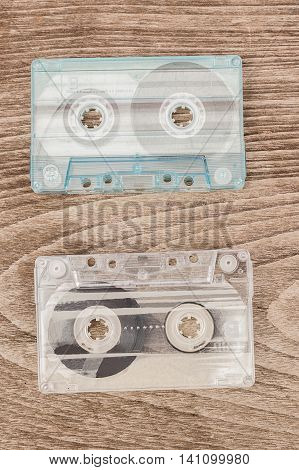 Old audio collection cassettes on wooden background.