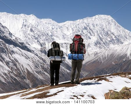 Two trekkers and mount Tilicho round Annapurna circuit trekking trail Nepal
