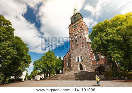 Turku Cathedral on sunny day with blue cloudy sky in background and square in foreground