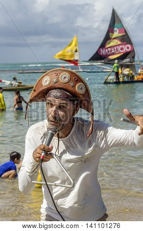 Pernambuco Brazil July 6 2016: An unidentified singer in Chicken Beach with typical sail boats behind in Ipojuca City near barrier reef northeast Brazil